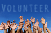 Volunteers raise their hands up to give back.