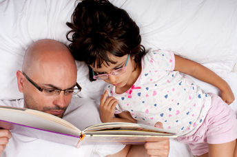 A father reads his daughter a bedtime story