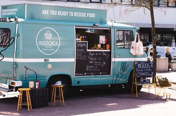 A food truck of the instock restaurant stands by the street