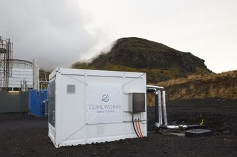 Direct air capture unit along with the cooling towers of the geothermal power plant in Hellisheidi, Iceland.