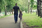 Father and small daughter walk in the park