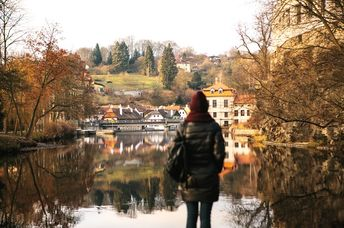 The girl tourist with backpack standing on the shore and enjoy the nature and views of the city. The reflection in the water. The concept of travelling solo