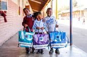 Three African children proudly show off their new Repurpose Schoolbags