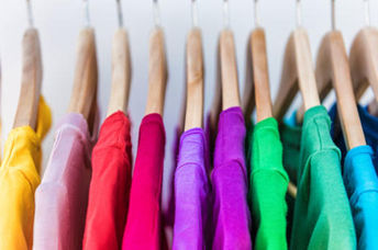 Shirts in different colors hang in a closet.