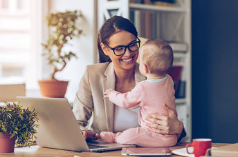 Cheerful young beautiful businesswoman looking at her baby girl with smile while sitting at her working place