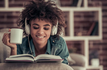 Afro American girl in headphones is listening to music, reading a book, drinking coffee