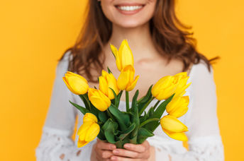 Photo of happy woman holding flowers to illustrate kindness