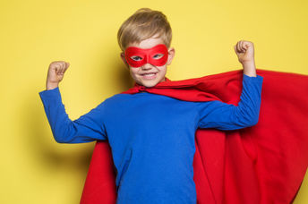 A young boy wearing a superhero mask and cape flexes his muscles and feels strong.