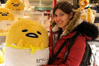 Young woman holds a large Gudetama plush toy.