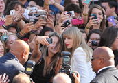 Taylor Swift surrounded by fans.