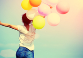 Happy woman jumping for joy with balloons