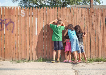 Curious children looking through fence