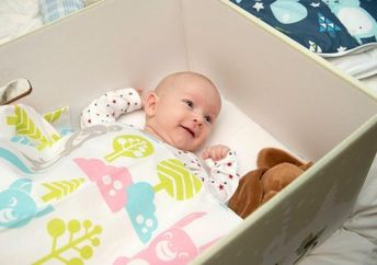 A baby models the box from the 2015 maternity package (Photo: Kela/Annika Söderblom)