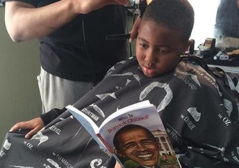 A boy reads about President Obama while getting his hair cut. (The Fuller Cut)