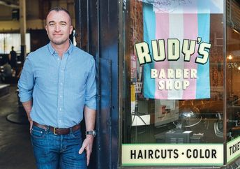 Brendon Lynch, CEO of Rudy's stands in front of a Rudy's branch with an LGBTQ flag in the window. (Rudy's Barbershop)