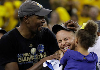 Kevin Durant (left) and Stephen Curry of the Golden State Warriors celebrate with Curry's daughter after winning the 2017 NBA Finals.
