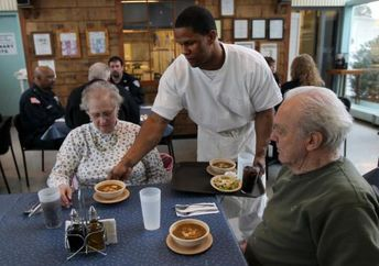 Northeast Correctional Center inmate Calvin Hodge serves lunch to Jacqueline Friedman and Walt Tetschner at the Concord facility's public restaurant, the Fife and Drum. (Bill Greene/Globe Staff)