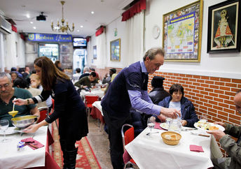 Volunteers serve free dinner to homeless people at Robin Hood restaurant in Madrid. (Pablo Blazquez Dominguez/Getty Images)