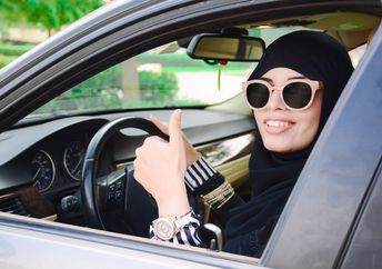 Happy business arabic lady in dark abaya and hijab driving her car and showing thumb up. Smiling arabian lady in sunglasses taking steering wheel of her new car.