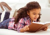 Young girl with curly hair reading a book on the floor