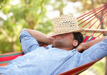 Man relaxing in hammock with hat covering his face