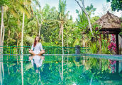 Woman meditation at gorgeous pool side of luxury tropical villa