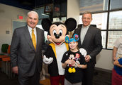 Mark A. Wallace, President and CEO of Texas Children's Hospital (left) and Disney Chairman and CEO Robert A. Iger (right) were joined by Mickey Mouse and hospital patients at an event taking place at Texas Children's Hospital.