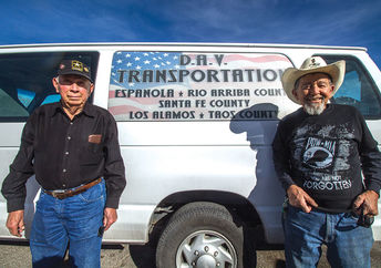 Mel Ortega (left) and Bernardo Jaramillo (right) stand, March 21, in front of the van they use to transport disabled veterans.