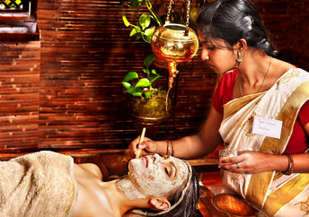 Woman having facial mask at ayurveda spa.