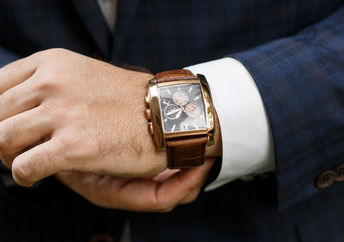A closeup of designer watch on a businessman's hand