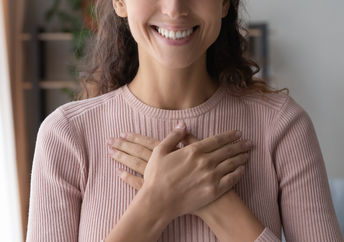 A woman smiles after receiving a compliment.