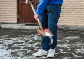 A man with a shovel spreads salt on an icy driveway.