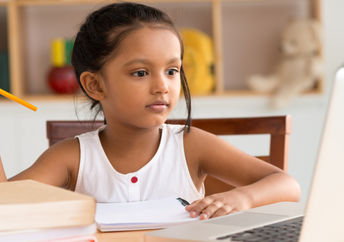 Khan Academy helps students with remote learning like this young girl studying online at home.