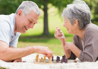 Retired couple playing chess, a brain game.