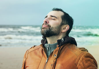 A man on the beach doing a breathing practice.