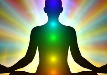 Aura colors and glowing chakras on a man who is meditating.