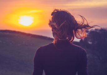 Woman on a mindfulness-inspired awe walk admiring the sunset
