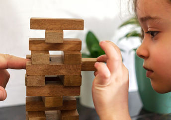 As a father and daughter play tumble tower, dad models resilience by assisting her in strengthening the tower.
