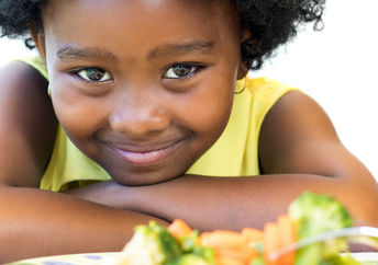 A young girl with a plate of healthy food smiles.