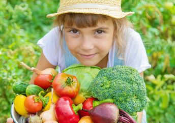 A young girl in a field holds a basket filled with freshly-picked vegetables.