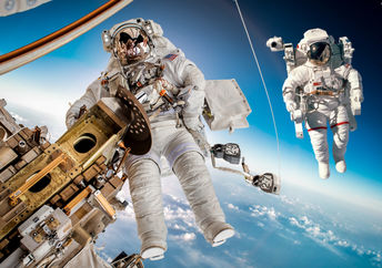 The International Space Station in outer space with two astronauts floating outside.