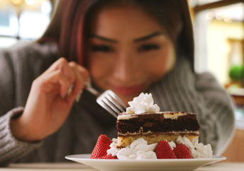 A woman happily indulges in a fancy dessert.
