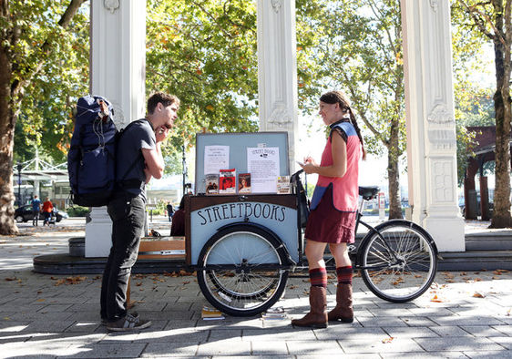 Laura Moulton pedals her bicycle-powered Street Books library to locations around Portland, Oregon, providing books to the city's homeless, who don't qualify for library cards.