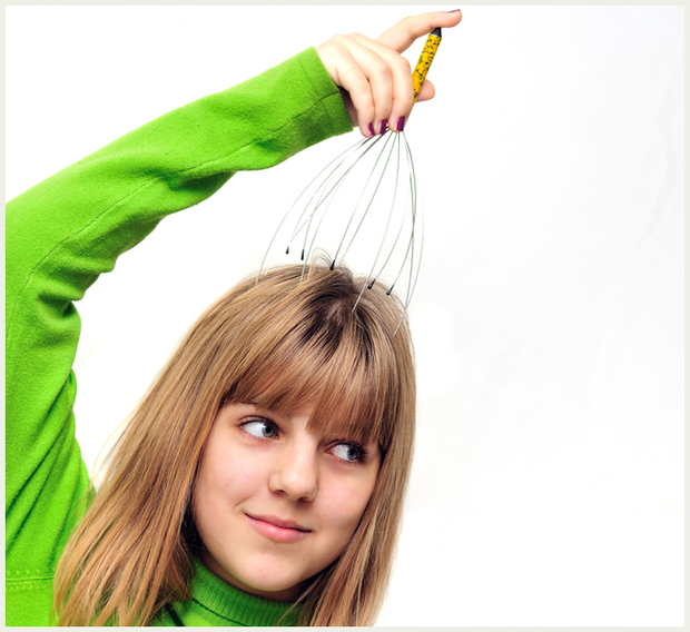 A girl massaging her head with a scalp massager or head tingler.