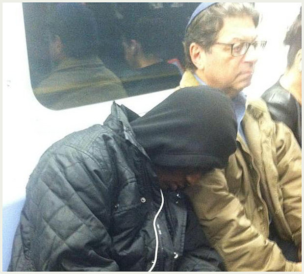 Older man lets younger man fall asleep on his shoulder on the subway.