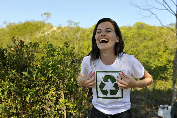 A happy volunteer wearing a recycle shirt.
