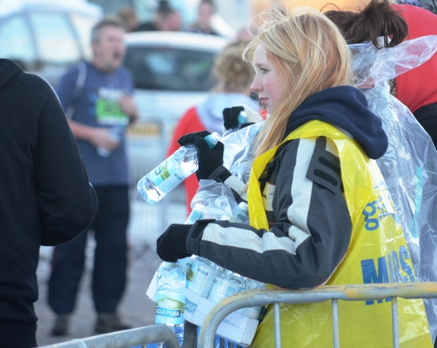 A volunteer supplying runners with cold water at a race.