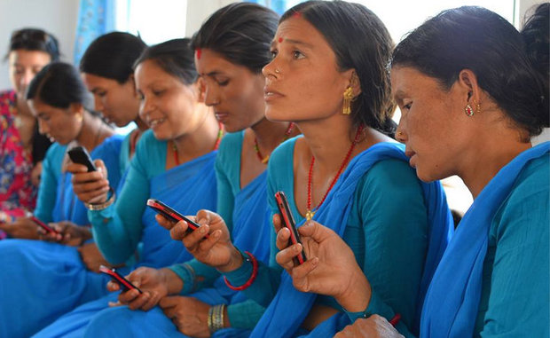 Community health workers in Nepal learning about how they can treat their patients more effectively by using a cell phone.
