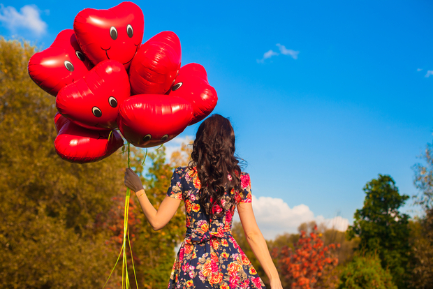 Woman wears floral dress and holds smiley balloons