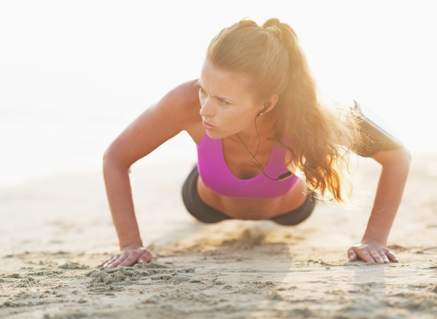 Woman does push ups on sand